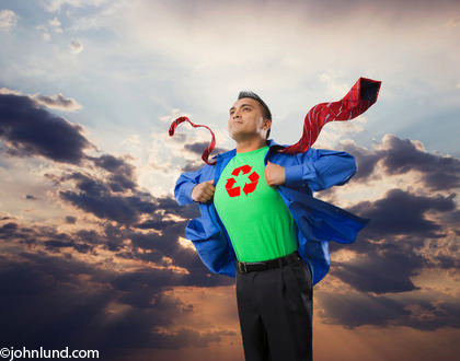Picture of a superhero with a recycling symbol on his chest for use in issues dealing with ecological and environmental issues. Resembling superman poses this superhero is ripping open his shirt to expose his costume underneath.